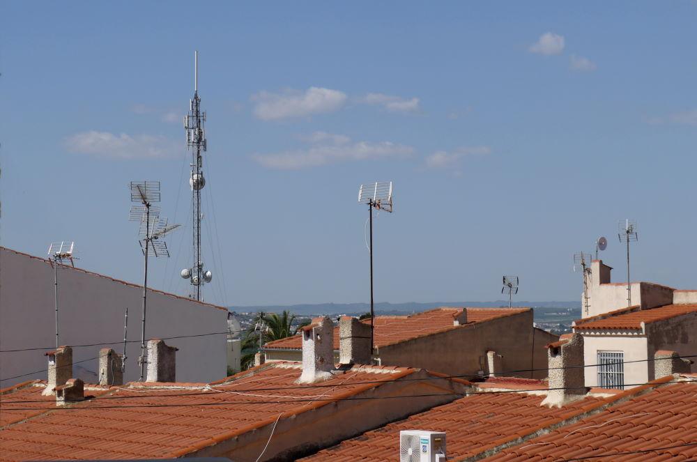 mobiilverkko tukiasema talojen katolla olevien antennien keskellä
